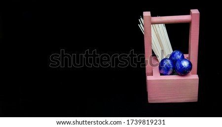 painted chicken eggs in a pink wooden basket and spaghetti on a black background. Easter holiday. Place for the text. Big picture. Banner.