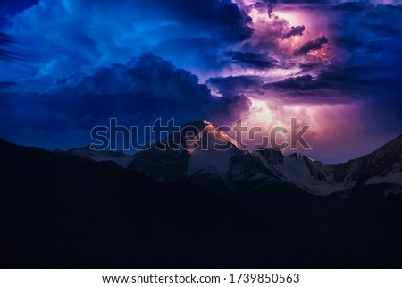 A picture of a bolt of lightning near the top of a mountain