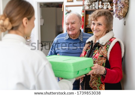 Senior couple greeting volunteer woman delivering a hot meal to their door Royalty-Free Stock Photo #1739853038