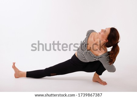 woman practices yoga in black leggings on a white isolated background. international yoga day