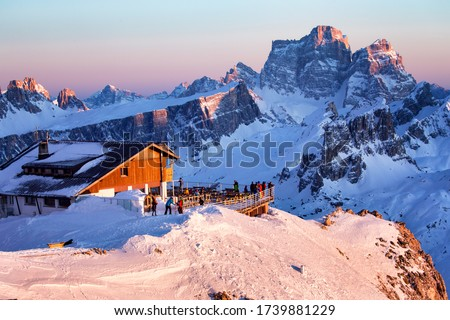 Rifugio Lagazuoi and Cable car station against the background of the Dolomites at sunset. Winter Alps near Cortina d'Ampezzo, Veneto, Italy. Postcard, Falzarego Pass, Dolomiti. Famous observation deck #1739881229