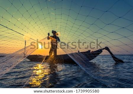 Fisherman net sunset Silhouette boat Royalty-Free Stock Photo #1739905580