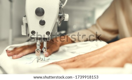 Close up of seamstress hands. She is sitting and sewing. Dressmaker working on the sewing machine. Tailor making a garment. Hobby sewing as a small business concept. Horizontal shot. Web Banner Royalty-Free Stock Photo #1739918153