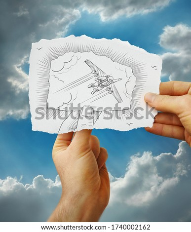 Futuristic man with wings flying in the sky drawn on a hand held piece of paper with clouds and blue sky in the photo background. Mixed media image