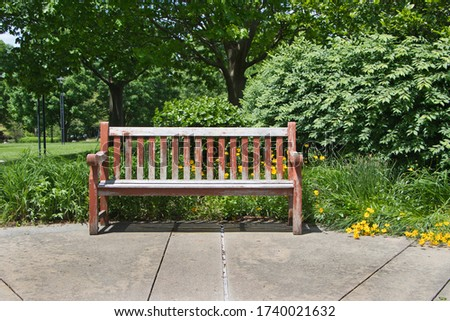 Park bench along walkway with flowers and bushes behind, #1740021632
