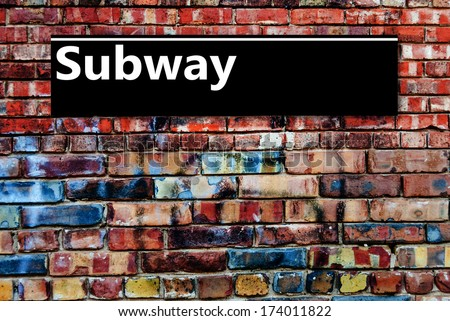 Subway or Underground sign board on a graffiti laden brick wall #174011822