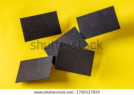 Thick black business cards, flying on a yellow paper background, a mock-up for a creative design presentation