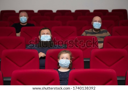 People in cinema with protection mask keeping distance away to avoid physical contact.Coronavirus COVID-19 disease protection.Social distancing practice #1740138392