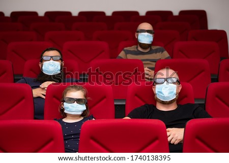 People in cinema with protection mask keeping distance away to avoid physical contact.Coronavirus COVID-19 disease protection.Social distancing practice #1740138395