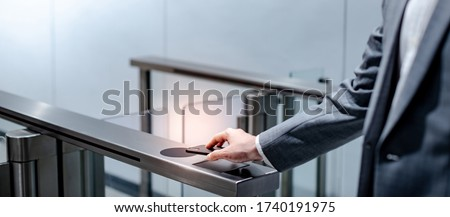 Businessman hand with business wear using smartphone to open automatic gate machine in office building. Working routine concept Royalty-Free Stock Photo #1740191975