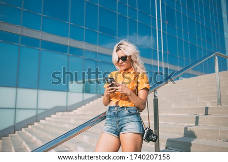 Youthful amateur photographer with camera reading article with advices for creating media content, millennial hipster girl in sunglasses installing filter application for editing photo pictures