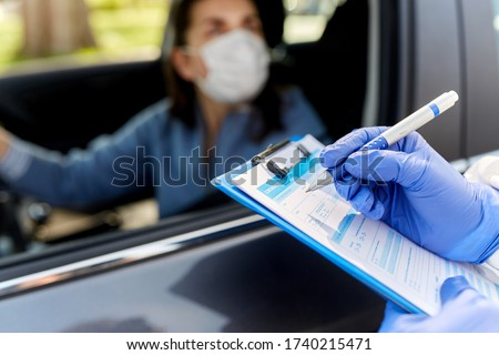 medicine, quarantine and pandemic concept - close up of doctor or healthcare worker in protective medical gloves writing to clipboard and woman waiting for coronavirus test in her car Royalty-Free Stock Photo #1740215471