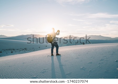 Image of young man tourist standing on dune top during sunset using mobile phone for taking picture of beautiful breathtaking nature scenery, hipster guy traveler taking pictures of desert on cellular