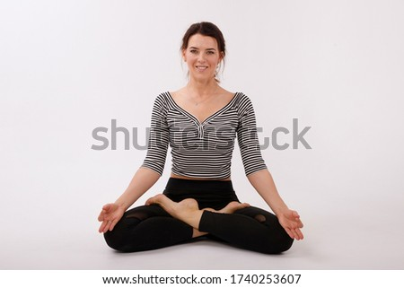 woman in lotus position on a white background isolated. black sports leggings and top. international yoga day