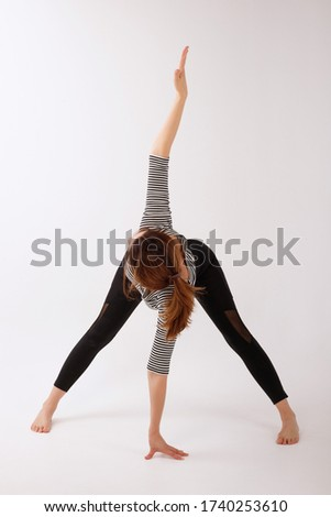 healthy woman in black sports leggings stretching on a white isolated background. yoga day