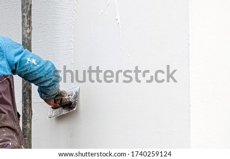 Construction worker plaster the facade of the house. Application Of Facade Plaster. Elevation of the building.  Royalty-Free Stock Photo #1740259124