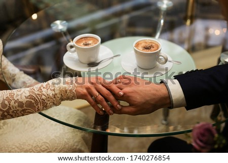 Touching hands of groom and bride near two cups of coffee. Wedding day concept. Wedding picture. Love is.