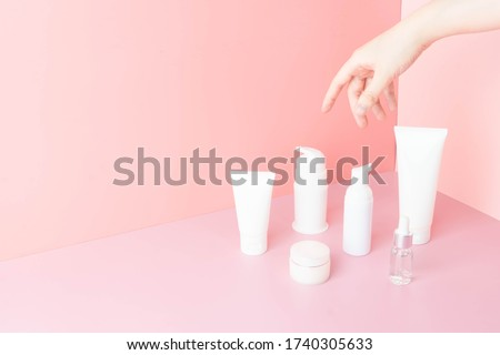Skincare routine- Women hand choosing skin care products for healthy skin on pink background. Packaging of facial foam, cleansing, essence, serum, cream/lotion. Beauty and cosmetic concept. Minimal. #1740305633