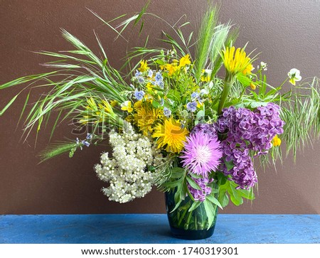 A large bouquet of bright multi-colored wild flowers in a decorative vase on a brown background.Free space.Defocus light background.