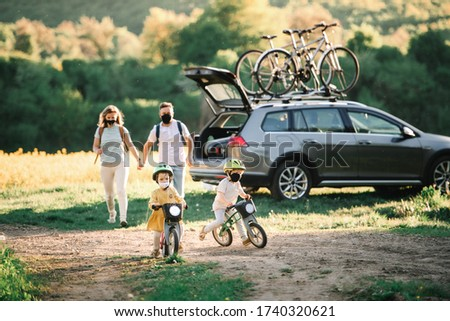 Family with two small children and face masks going on cycling trip in countryside. Royalty-Free Stock Photo #1740320621