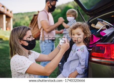 Family with two small children loading car for trip in countryside, wearing face masks. #1740320666