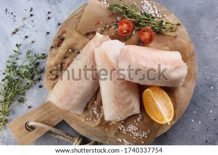Seafood. White fish, cod fillet with thyme, spices, salt, tomatoes and lemon on a wooden board on a light grey background. Flatlay, top view. Background image, copy space
