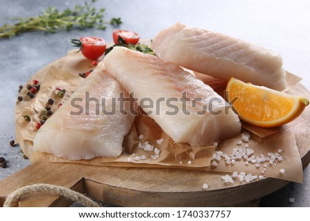 Seafood. White fish, cod fillet with thyme, spices, salt, tomatoes and lemon on a wooden board on a light grey background. Background image, copy space
