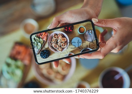 Top view of young hipster girl taking picture on smartphone trendy homemade breakfast with tasty pancakes, berries, Female Food Blogger sharing photo of breakfast in social networks, Delivery Service