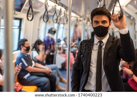 Portrait of confident businessman in black suit wear mask in city finding job during corona crisis using smartphone travelling on empty train Royalty-Free Stock Photo #1740400223