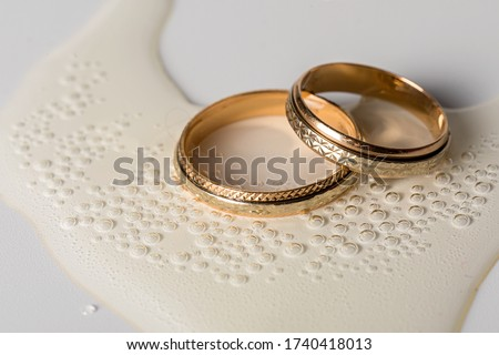 Wedding golden rings in glass of champagne. Symbol of love and marriage. Creative picture with champagne bubbles, glittering in the sunlight.