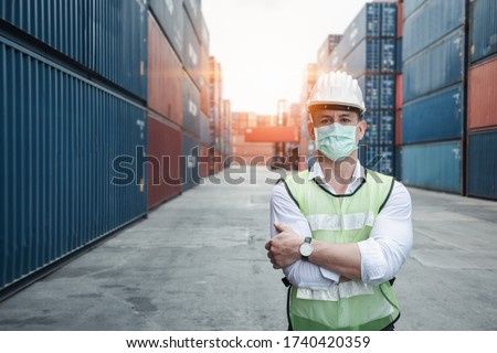 Transport Engineer Man Wearing Medical Face Mask for Prevention Coronavirus Epidemic Situation in Containers Logistic Shipping Yard. Transportation and Logistics after Coronavirus Covid-19 New Normal #1740420359