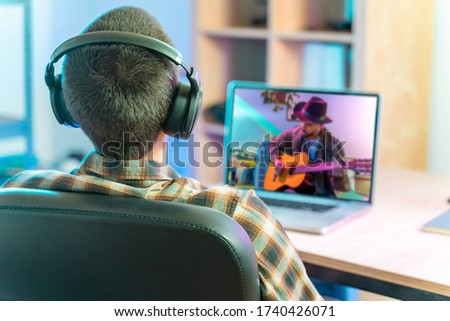 Coronavirus. Back view of man watching live video concert while staying at home. Close up of a man enjoying musical concert on laptop. Stay at home. Quarantine. Isolated. #1740426071
