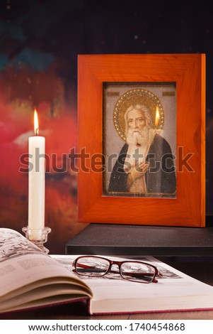 burning candle with an open book and glasses, a picture on the table in the evening