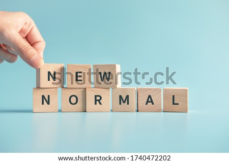 Woman hand arranging wooden cubes with NEW NORMAL word. Adapting to new life or business post-lockdown after coronavirus pandemic. Business with social distancing personal hygiene. Royalty-Free Stock Photo #1740472202