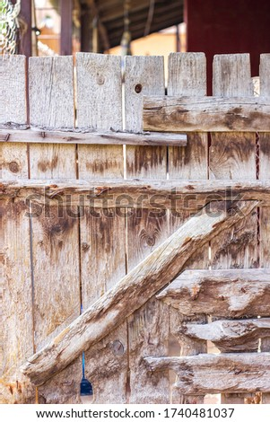 Old wooden gate in fence. Part of wood brown shed door, soft focus #1740481037