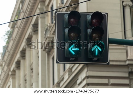 An automated traffic light in the city turned green. Arrow signs are showing straight and left directions to go ahead and move on.