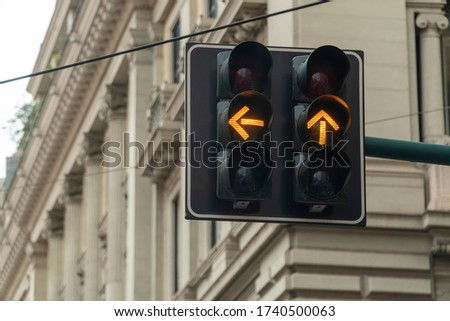An automated traffic light in the city turned yellow. Arrow signs are showing straight and left directions to prepare to stop or to move on. Caution