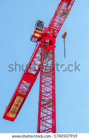 Detail of red Lifting Crane with the blue sky in the background. Red heavy industrial machinery in work. House Building, apartment construction. Building Business. Colorful industry background. #1740507959