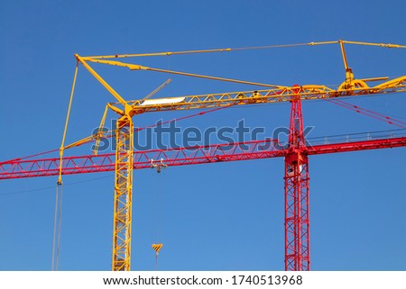 Close up of a yellow crane and a red crane against clear blue sky. Colorful industry background. Cranes are machines used for moving objects. #1740513968