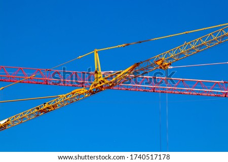 Close up of a yellow crane and a red crane against clear blue sky. Colorful industry background. Cranes are machines used for moving objects. #1740517178
