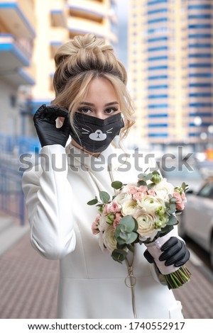 Beautiful bride with wedding flowers bouquet, attractive woman. Bride in mask and glows, which protect her from virus. Bride in the city on the street. #1740552917