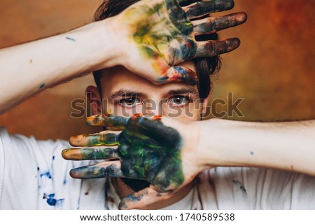 The artist creates a frame with his hands soiled with watercolor paints. Portrait of a young creative artist, the process of creating a picture. Copy space