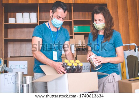 Two people working in charitable foundation helping in disasters,packing food and clothes.Volunteers with protective mask working on donation project support in economy crises  #1740613634
