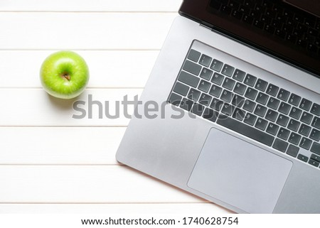 Laptop keyboard and green apple on white wooden table. Top view. Concept distance learning Royalty-Free Stock Photo #1740628754