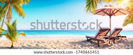 Chairs And Parasol With Palm Trees In The Tropical Beach  Royalty-Free Stock Photo #1740661451