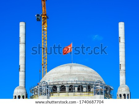 Crane builds up new turkish mosque in istanbul. The dome, minarets and a crane on a background of blue sky #1740687704