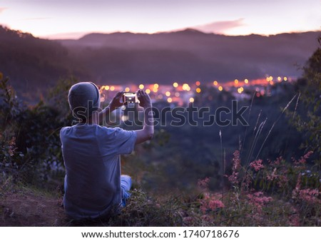 Young man taking pictures with Smartphone of city lights under twilight sky