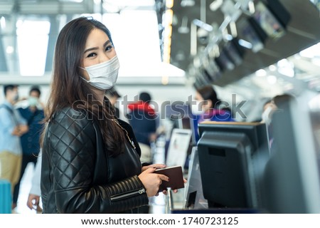 Asian female traveler holding passport at customer check in of airline service counter. New normal, woman wearing face mask when traveling by airplane transportation to prevent covid19 virus infection #1740723125
