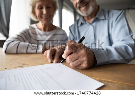 Close up focus on wrinkled male hand signing paper document. Smiling elderly mature family couple putting signature on leasing or medical insurance contract, purchase agreement with real estate agent