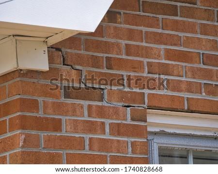 Cracked Brick Foundation, house settling causing bricks crack Royalty-Free Stock Photo #1740828668